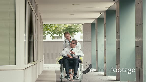 Disabled Man Using Wheelchair In Hospital With Doctor 12145