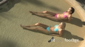 LS PAN OF TWO WOMEN SUNBATHING BY A SWIMMING POOL 13566
