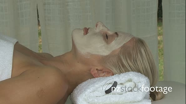 MCU OF A BEAUTICIAN APPLYING A FACE MASK TO A WOMAN 13576