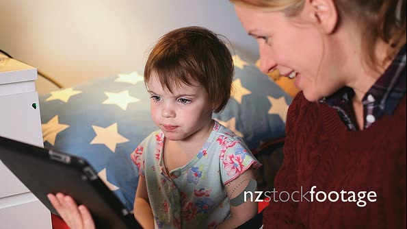 Mother using digital tablet with girl 13846