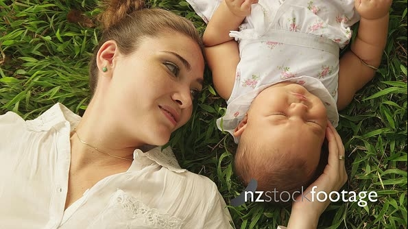 Mother Kissing Little Baby Daughter Laying Closed On Grass 14281