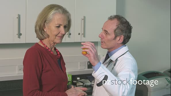 Doctor giving pill bottle to patient 14423