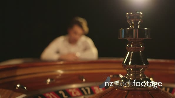 MS A Young Man sips his drink, the Roulette Table in focus in fo 14723