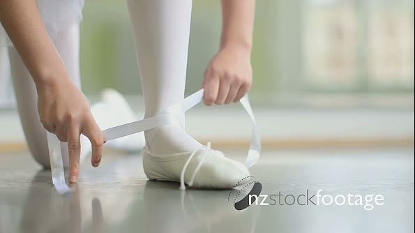 CU A young Ballerina ties the ribbons of her sof top Ballet Shoe 16335