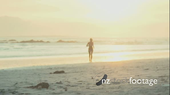 SLO MO WS OF A YOUNG WOMAN RUNNING ON A BEACH 17939