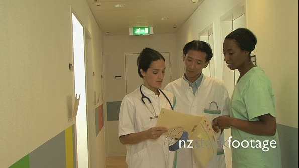 MS ZI OF DOCTORS AND A NURSE READING A FILE 18398