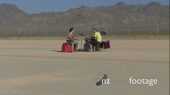 Male and female playing music in desert and walking away 18476