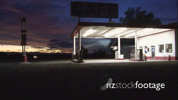 Abandoned petrol station at night with car passing by 18492