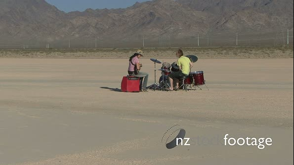 Male and female playing music in desert and walking away 18502