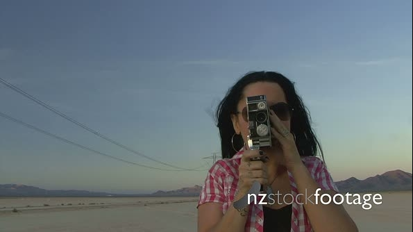 Female in desert using a cine camera 18517