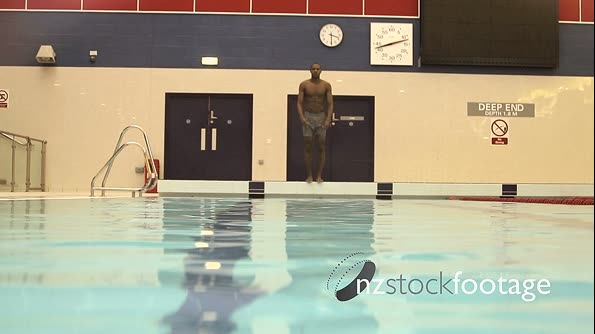 Male jumping into swimming pool in gym 20466