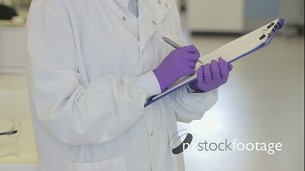 Portrait of Female writing down notes on notepad in science laboratory and looking to camera 20564