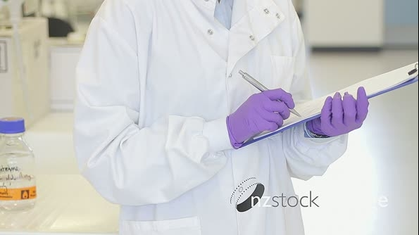 Portrait of Female writing down notes on notepad in science laboratory and looking to camera 20580