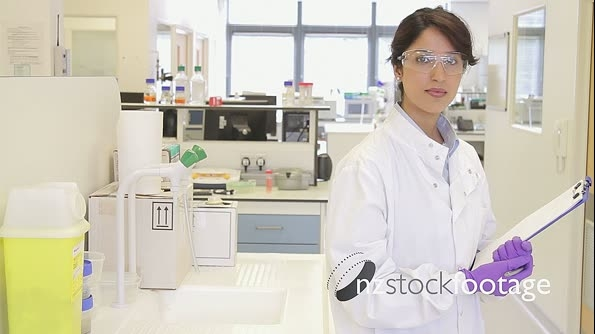 Portrait of Female writing down notes on notepad in science laboratory and looking to camera 20584