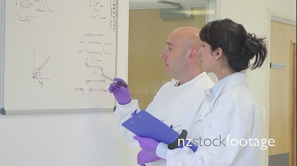 Scientist analyze and discuss research data on white board in science laboratory 20592