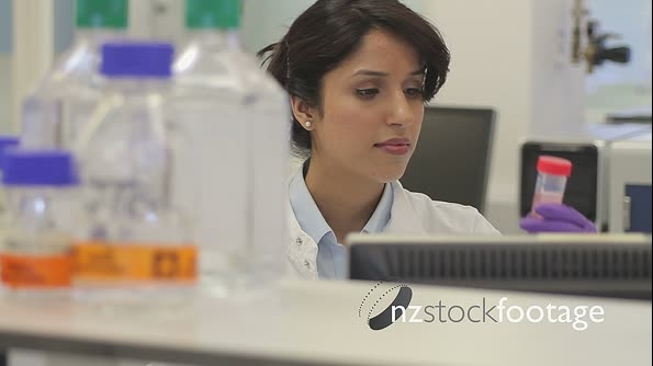 Female looking at computer screen and test tube in laboratory 20607