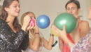 Females friends blowing up balloons at party 20674