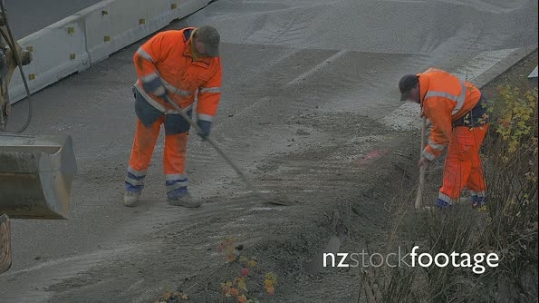 Two construction workers shoveling gravel on highway 22477