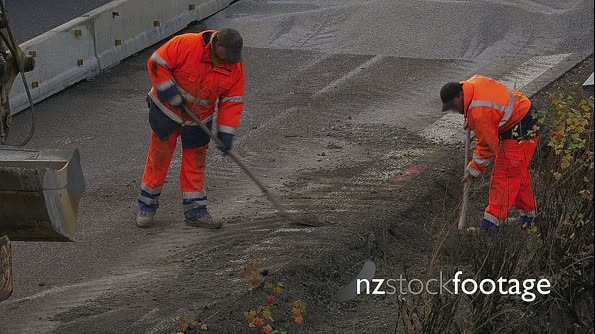 Two construction workers shoveling gravel on highway 22487