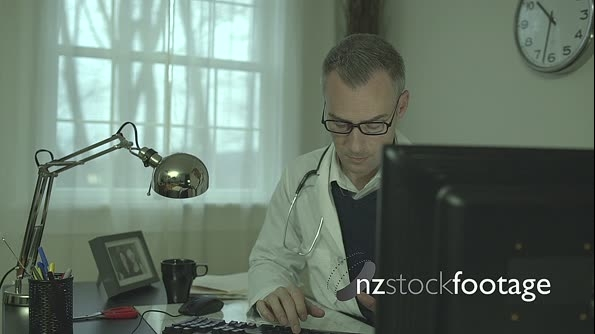 Serious doctor at his office desk 26532
