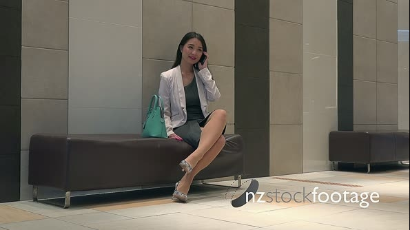Elegant Asian Woman Talking On Mobile Phone In Office Building 26679