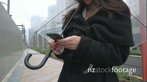 Technology With Asian Woman Texting Using Smartphone In The Rain 26682