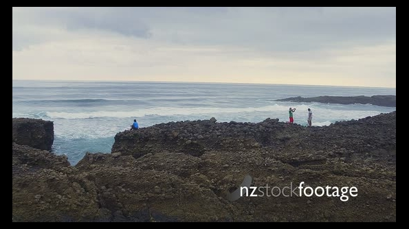 aerial of people fishing off rocks at karekare beach, Auckland, New Zealand 26704