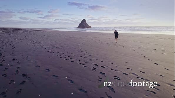 Aerial Of woman walking and running on a beach, karekare, Auckland, New Zealand 26973