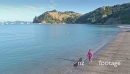 Aerial of woman walking on calm beach on waiheke island, New Zealand 27000