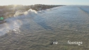 Aerial tracking view of a large wave as it travels towards houses on the coast 28094