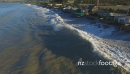 Aerial view of large waves slamming into coastal properties 28095