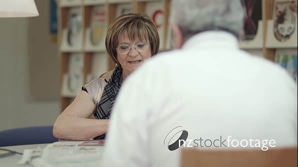 Old Woman Reading Newspaper With Husband In Library 6301