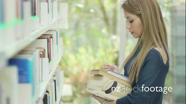 Student Choosing Book In University  Library 7420